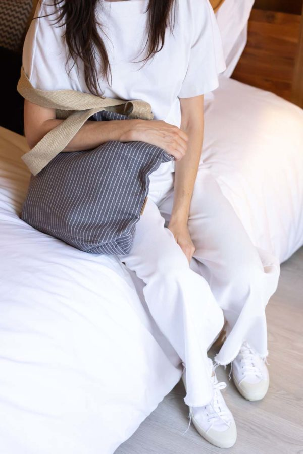 Mujer sentada en una cama con una bolsa tote de algodón reciclado