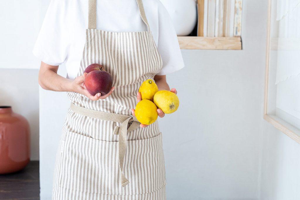 Mujer con manzanas y limones en las manos lleva puesto delantal algodón reciclado verdonce