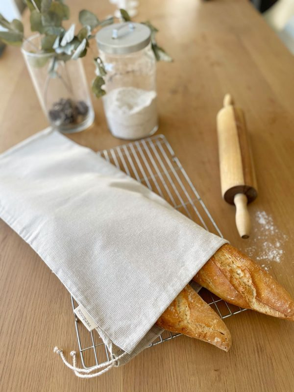 Bolsa de pan reutilizable con dos barras de pan en la mesa