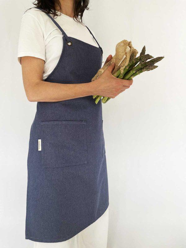 Mujer lleva delantal denim reciclado verdonce con verduras
