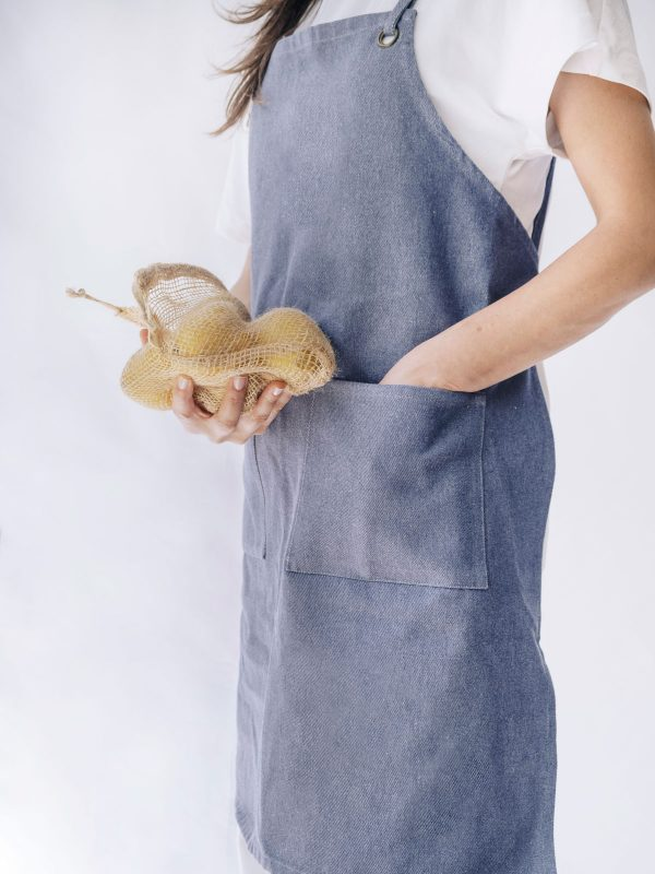 Mujer lleva delantal denim reciclado verdonce con bolsa de yute y limones