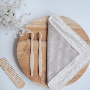 toalla tocador en una tabla de madera con cepillos de dientes bambú